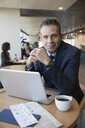 Portrait confident businessman working and drinking coffee at laptop in airport lounge - HEROF30262