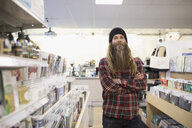 Portrait confident hipster with long beard in music store - HEROF30280