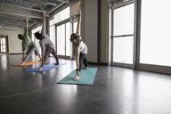 Men and woman practicing yoga triangle pose in yoga class studio - HEROF30283