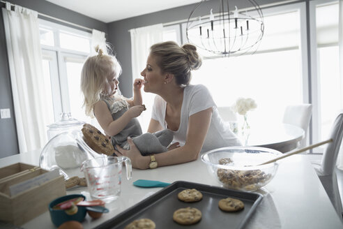 Mother and daughter baking, eating fresh cookies in kitchen - HEROF30319