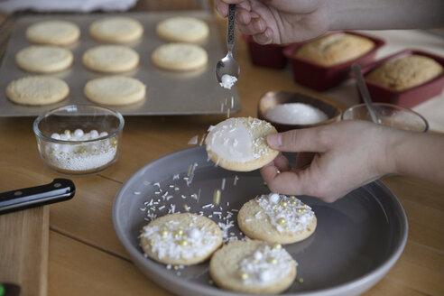 Woman decorating Christmas cookies with sprinkles - HEROF30376