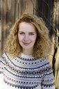 Blonde woman with curly hair smiling, norwegian sweater - ECPF00605