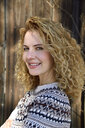 Blonde woman with curly hair smiling, norwegian sweater - ECPF00608