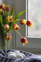 White eggs in kitchen towel with tulips in the background - MELF00202