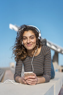 Young woman lying on a wall listening music with headphones on her smartphone - AFVF02610