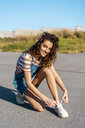 Young woman sitting on ground tying shoes - AFVF02613