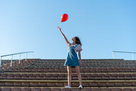 Young woman standing on granstand, letting go of a red ballon - AFVF02616