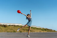 Young woman holding red ballon, dancing - AFVF02619