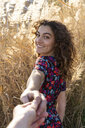 Young woman standing in meadow, holding hand of a young man - AFVF02622