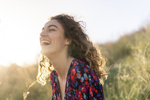 Portrait of a young woman standing in meadow, laughing - AFVF02634