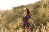 Happy young woman standing in summer meadow - AFVF02637