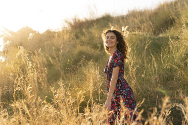 Happy young woman standing in summer meadow - AFVF02640