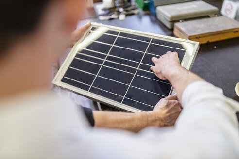 Close-up of two colleagues in factory working on solar cell - DIGF06240