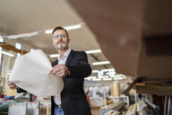 Businessman with plan in factory warehouse - DIGF06255