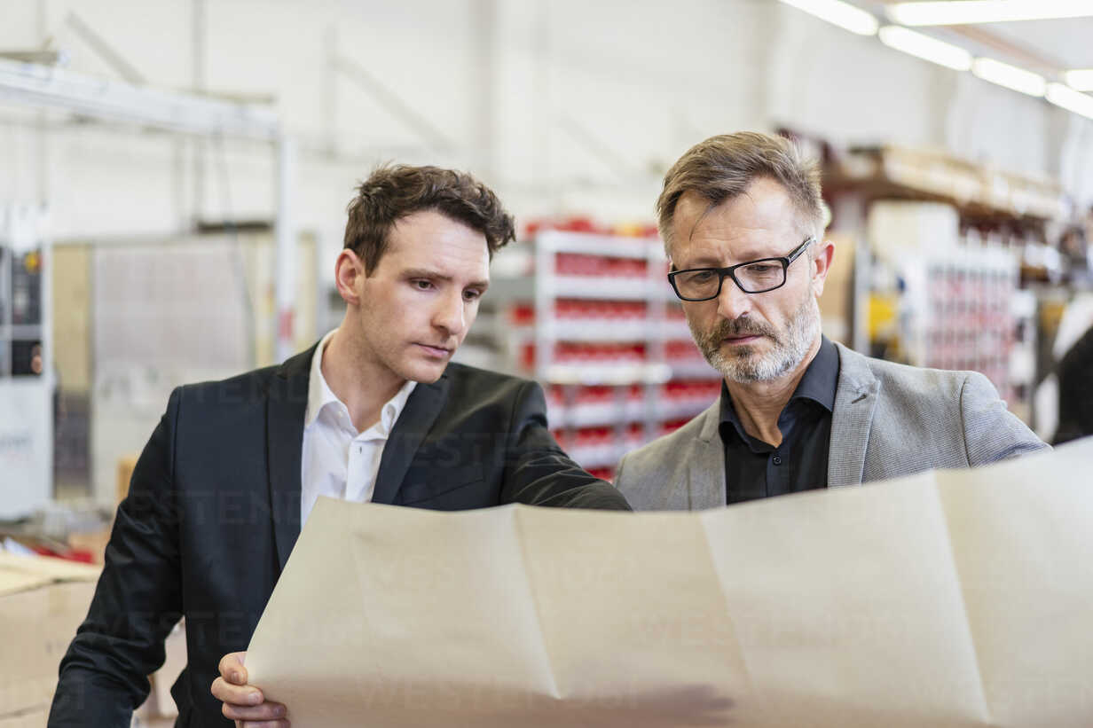 Two businessmen discussing plan in a factory - DIGF06267 - Daniel Ingold/Westend61