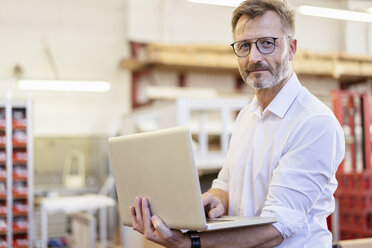 Portrait of confident businessman using laptop in factory - DIGF06315