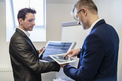 Two businessmen in office with solar cell and tablet - DIGF06318