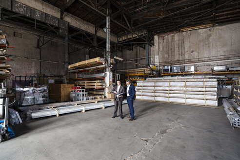 Two businessmen with folder talking in an old storehouse - DIGF06324