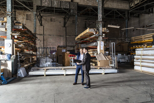 Two businessmen with folder talking in an old storehouse - DIGF06327