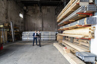 Two businessmen with folder talking in an old storehouse - DIGF06330
