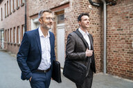Two smiling businessmen walking at an old brick building - DIGF06333