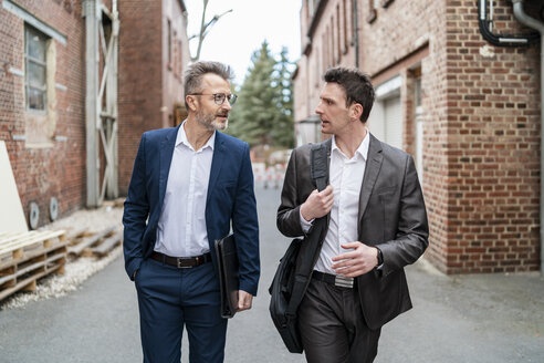 Two businessmen walking and talking at an old brick building - DIGF06336