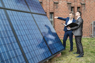 Two businessmen talking outside brick building at solar panels - DIGF06339