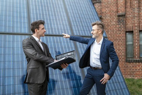 Two businessmen talking outside brick building at solar panels - DIGF06342