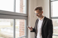 Businessman using cell phone at the window in office - DIGF06360