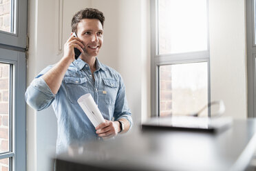 Smiling businessman on cell phone at the window in office - DIGF06366