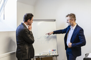 Two businessmen in office discussing at flip chart - DIGF06381