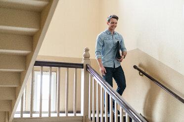 Smiling man walking down stairwell - DIGF06405