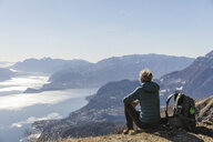 Italy, Como, Lecco, woman on a hiking trip in the mountains above Lake Como sitting down enjoying the view - MRAF00372