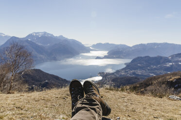 Italy, Como, Lecco, close-up of woman on a hiking trip resting in the mountains above Lake Como - MRAF00375