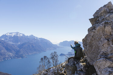 Italy, Como, Lecco, woman on a hiking trip in the mountains above Lake Como sitting on a rock enjoying the view - MRAF00384