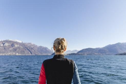 Italy, Como, rear view of woman enjoying the view of Lake Como - MRAF00399