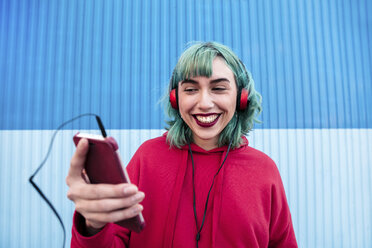 Portrait of laughing young woman with blue dyed hair with headphones taking selfie with smartphone - LOTF00065