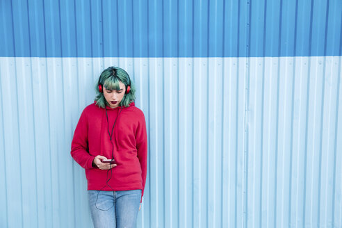 Young woman with blue dyed hair listening music with headphones while looking at smartphone - LOTF00068