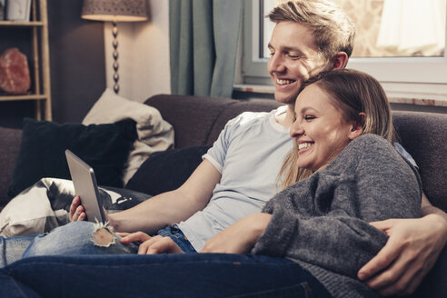 Happy young couple using tablet on couch at home - SEBF00086