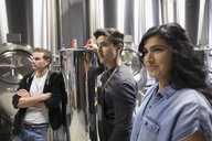 Confident brewers looking away next to vats in brewery - HEROF30443