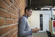Businessman texting with cell phone against brick wall in office - HEROF30470