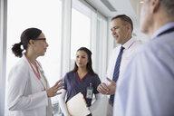 Doctors and nurse consulting in clinic corridor - HEROF30557