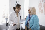 Caring female doctor talking with senior patient in clinic examination room - HEROF30566