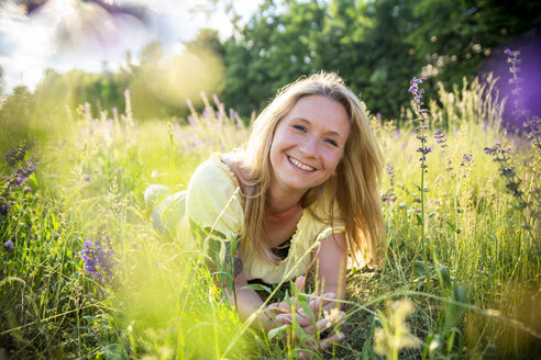 Portrait of happy blond woman lying on flower meadow in summer - SARF04174