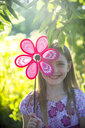 Portrait of laughing girl hiding behind pinwheel - SARF04177