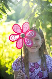 Portrait of laughing girl hiding behind pinwheel - SARF04177