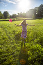 Happy girl with pinwheel running on summer meadow - SARF04180