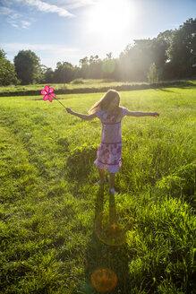 Mädchen mit Windrad, dreht sich in einer Sommerwiese, Landshut, Bayern, Deutschland - SARF04180
