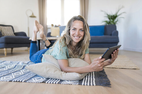Portrait of smiling woman lying on the floor at home using tablet - SBOF01909