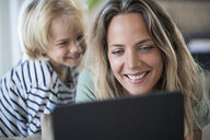 Smiling mother and son at home using tablet - SBOF01912